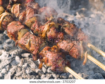 Kebabs cooking on the grill with smoke