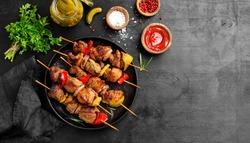 Kebabs - grilled meat skewers, shish kebab with vegetables on black wooden background.