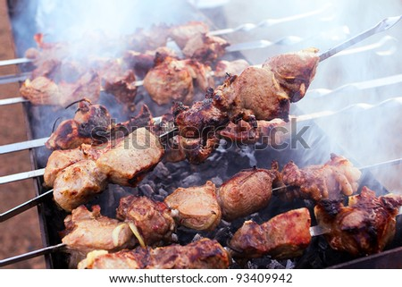 Kebabs on skewers cooked on the coals in the smoke