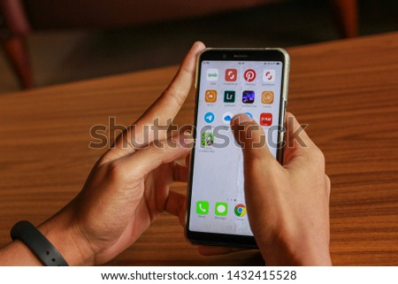 Kedah, Malaysia - June 2019: Man hand using his smartphone application. Man sitting alone in the cafe with wooden table. #1432415528