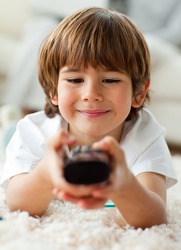 Keen little boy holding a remote lying on the floor in the living-room
