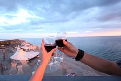 keep a glass of wine at sunset sea at the height of the tower