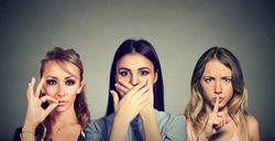 Keep a secret be quiet concept. Three secretive woman keeping mouth shut.