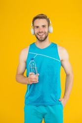 Keep body and mind in good shape. Happy sportsman hold water bottle. Fitness trainer. Feeling thirst. Thirst and dehydration. Thirst control. Drinking water. Cheerful athletic guy listening music.
