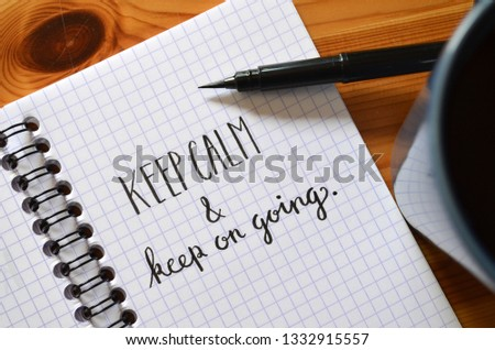 KEEP CALM and KEEP ON GOING written in notebook on wooden desk with cup of coffee