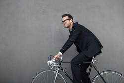 Keep calm and ride on. Cheerful young businessman smiling and looking away while cycling against grey background