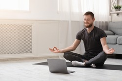 Keep calm on quarantine. Millennial guy meditating with trainer online via laptop connection, empty space