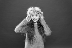 Keep head in warmth. Feeling warm. Child long hair soft hat. Winter fashion concept. Warm hat for cold winter weather. Kid girl red background. Soft furry accessory. Winter season. Shopping concept