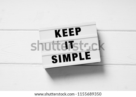 keep it simple text on lightbox sign, minimal flat lay design on white wooden background, simplicity or minimalism concept Foto d'archivio ©