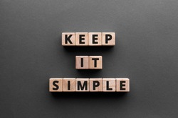 Keep it simple - word from wooden blocks with letters, to make something easy, keep it simple concept, gray background