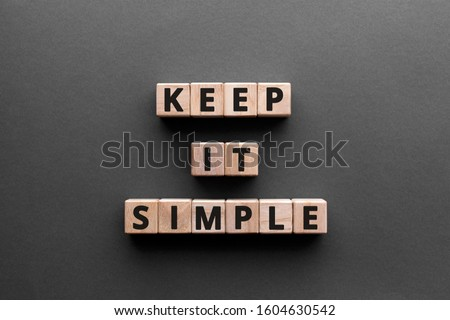 Keep it simple - word from wooden blocks with letters, to make something easy, keep it simple concept, gray background Foto d'archivio ©