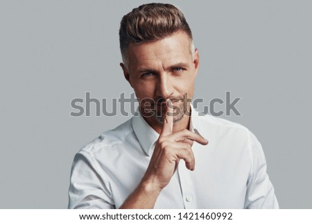 Keep my secret! Handsome young man looking at camera and keeping finger on lips while standing against grey background