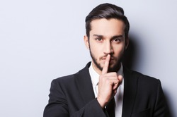 Keep my secret!  Serious young man in formalwear holding finger on lips and looking at camera while standing against grey background