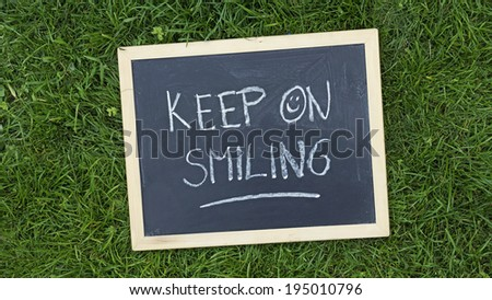 Keep on smiling written on a chalkboard in the nature