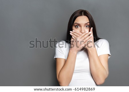 Keep silence. Scared woman covering mouth with hands while posing to camera on gray studio background. Shocked girl close lips with palms, speak no evil concept