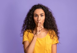 Keep silence. Serious young woman showing shhh sign at camera, holding finger near lips, mysterious brunette lady making hush gesture, standing over purple studio background, copy space