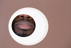 Keep silent. Copyspace. Lips of african-american man peeks throught circle in brown background. Trendy geometrical style, copyspace. Vibrant colors. Sales, proposal, finance and business concept.