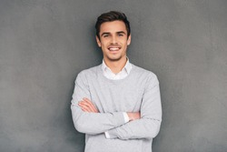 Keep smiling. Confident young man keeping arms crossed and looking at camera with smile while standing against grey background