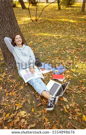 Keep smiling. Pretty female person leaning on the tree and keeping book on her knees