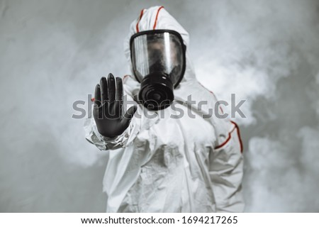 keep the distance, stop to coronavirus. disinfector male in gas-mask and protective suit disinfect contaminated areas full of bacterias. quarantine time