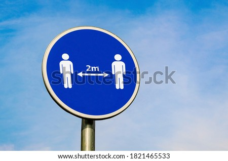 Keep two metres away. Safety distace icon on blue circular sign on the background of blue sky. Coronavirus epidemic social advice. 2 m rule. Zdjęcia stock ©