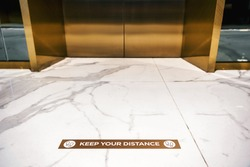 Keep your distance Text on the floor in front of lift or elevatorCovid-19 pandemic, new normal Concept, Keep your distance Text on the floor in front of lift or elevator