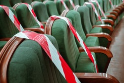 Keep your distance to avoid physical contact. Practice of social distancing. View of rows of seats marked with a warning tape in the cinema, theater, auditorium, conference hall. Protection COVID-19