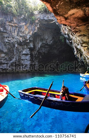 KEFALONIA, GREECE - JUNE 21 - Worker sat in his boat waiting for tourists to arrive in Melissani Cave, Kefalonia Greece.  The cave was discovered in 1951.  21 June 2007