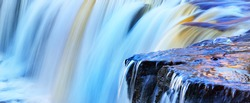 Keila waterfall texture, Estonia. Close-up, long exposure. Blue and white water splashes. Abstract natural pattern. Environmental conservation, travel destinations, graphic resource. Panoramic image