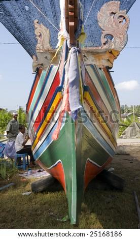 KELANTAN,  MALAYSIA - January 28:  Local Kelantanese fisherman paints the wooden fishing boat in Kelantan, Malaysia on January 28, 2009. The boats were handmade from south of Thailand.