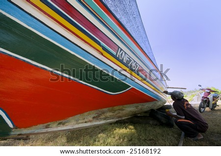 KELANTAN,  MALAYSIA - January 28:  Local Kelantanese fisherman paints the wooden fishing boat in Kelantan, Malaysia on January 28, 2009. The boats were handmade from south of Thailand.