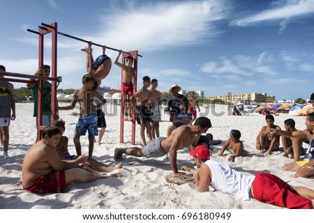 KELIBIA, TUNISIA - AUGUST 13, 2017: group of young people on the beach doing fitness and gym activity