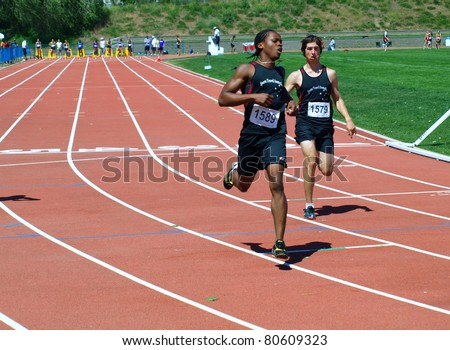 KELOWNA, CANADA - (L-R) Njemanze Adika and Cifra Stefan finish the 100 Meter Dash Final for boys age 15 on  July 3, 2011 at the Jack Brow Memorial Track & Field Meet in Kelowna, Canada