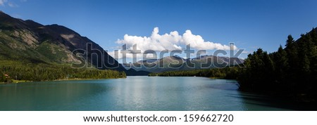 Kenai River in Alaska flows past forests and mountains in the wilderness