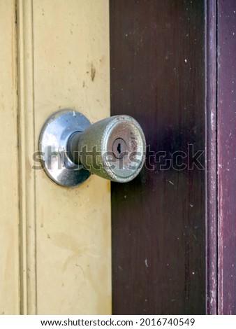 Kenop antik dengan lubang kunci terbuat dari logam yang menempel di pintu kayu yang dicat Stock fotó ©