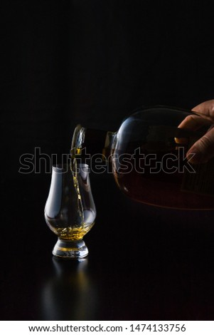 Kentucky straight bourbon whiskey being poured into a glencairn whicky glass in front of a black background. The glass reflections shine off the black wood surface. Portrait orientation with copy. #1474133756
