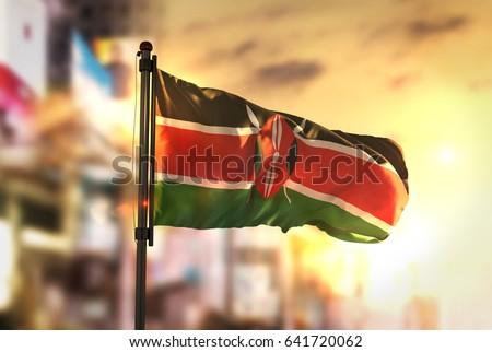 Kenya Flag Against City Blurred Background At Sunrise Backlight 3D Rendering