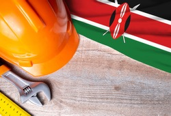 Kenya flag with different construction tools on wood background, with copy space for text. Happy Labor day concept.