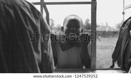 KENYA, KISUMU - MAY 20, 2017: Portrait of little african boy smiling, holding on lattice. Cute male spending time outside #1247539252