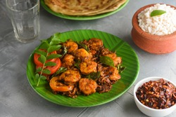 Kerala fish curry Prawns,Konju roast and Porotta or Chemmeen Ulathiyathu, shrimp fry Kerala fish curry spicy prawns in banana leaf plate on white background in South India. Popular Indian non veg food