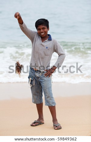 KERALA, INDIA - FEBRUARY 11, 2010: Young boy with poison lionfish poses for a photo on the shores of Arabian Sea