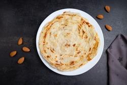 Kerala Porotta and beef curry, Malabari Parotta, meat roast dark black background India. Popular street food use Maida flour in Kerala, Tamil Nadu, Sri lanka. Top view of South Indian breakfast, snack