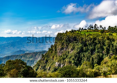 Kerio Escarpment, Great Rift Valley, Kenya, Africa. Landscape view of the tree covered escarpment, looking into the distance, to the mountains of the Great Rift Valley. Few clouds in sky. Copy space.  #1055333264
