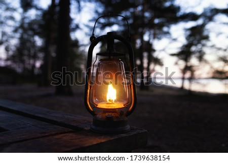 Photo of  Kerosene lamp at the lakeside. Beautiful colorful illuminated lamp in the forest in misty night. Vintage style lantern at night outdoor.