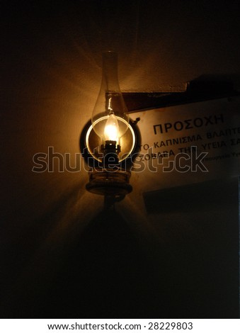 kerosene lamp hanging on a wall with a no smoking warning.