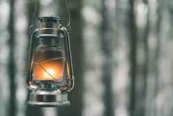 Kerosene lamp with light on blurred background of winter forest