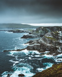 Kerry cliffs with green grass and dramatic clouds in cloudy summer day, Skellig Ring, Kerry, Ireland.