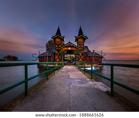 Keszthely, Hungary - The beautiful Pier of Keszthely by the Lake Balaton with a colorful autumn sunset. Famous touristic attraction in Zala county Stock photo ©