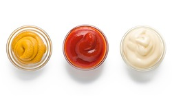 ketchup, mustard, mayonnaise in glass bowls on a white background. Traditional fast food and barbecue sauces.