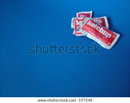 Ketchup packets on blue background